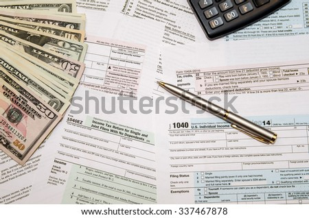 Filing federal taxes for refund - tax form 1040,  calculator, pen, dollar
