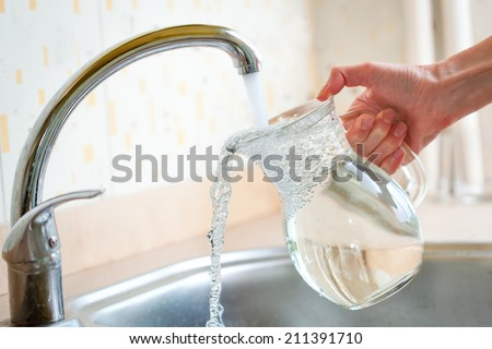 Filing glass pitcher with water from tap - stock photo