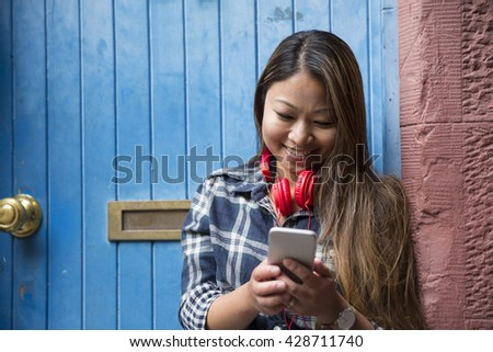 Filipino woman using her smart phone outdoors.