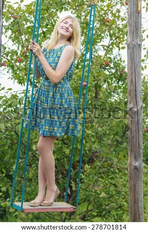 Fill length portrait of rideing blonde girl in blue silk sundress on handmade swing - stock photo
