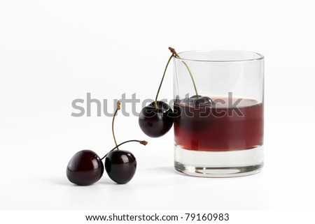 Filled glass and sweet  cherry on white background