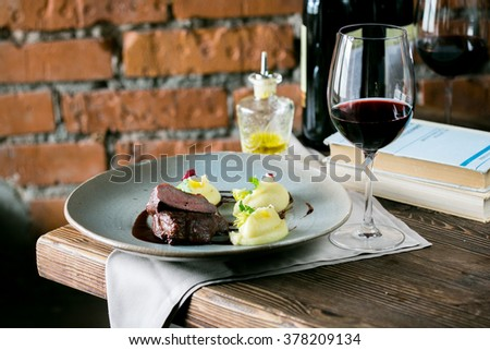 Fillet mignon with mashed potatoes on a glass of red wine on a wooden table, brick wall background - stock photo