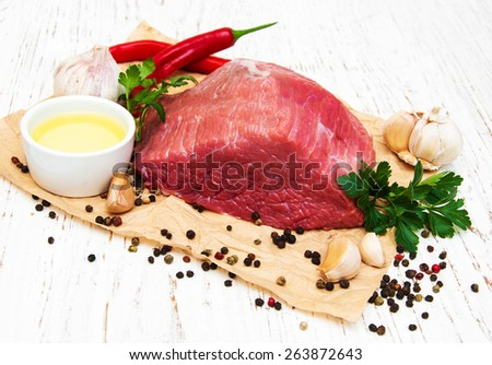 fillet of beef and ingredients on a old wooden background