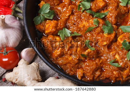 fillet of chicken in curry sauce with ingredients on an old table top view macro horizontal  - stock photo