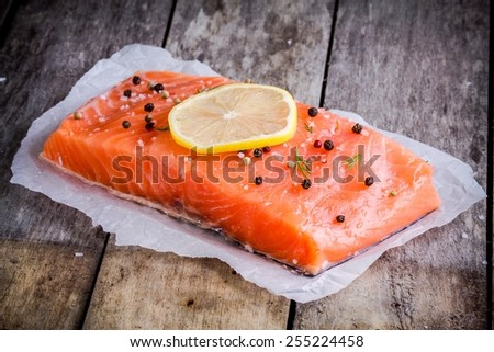 fillet of fresh salmon with pepper and lemon on wooden rustic background - stock photo