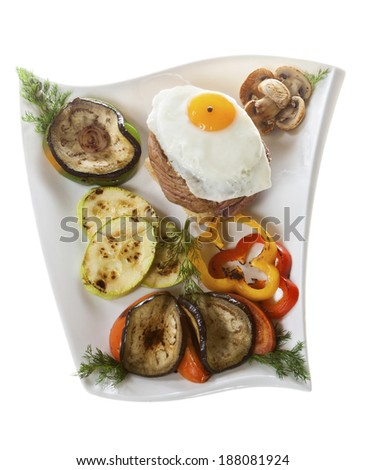 Fillet steak with egg and grilled vegetables on the plate. - stock photo