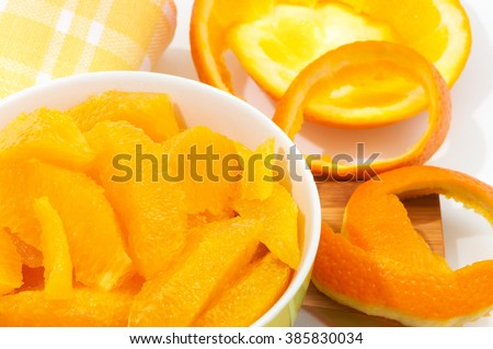 Fillets of oranges in porcelain dish decorated with orange peel and yellow kitchen towel; Ingredient for sweet dessert or marmalade; Juicy and tasty source of vitamins - stock photo