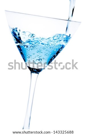 filling a glass with blue cocktail tilted and bubbles on a white background - stock photo
