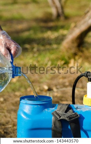 Filling a pesticide sprayer against the background of a citrus orchard - stock photo