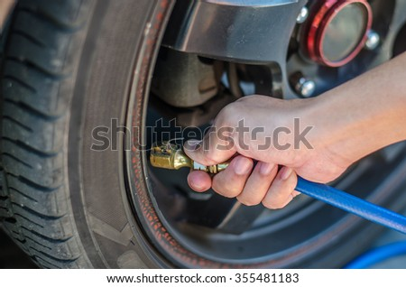 Filling air into a car tire in pump.
