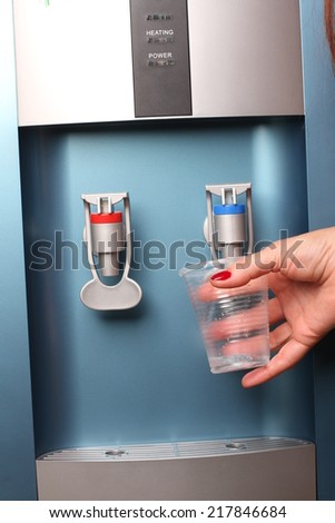 filling cup at water cooler, water dispenser - stock photo
