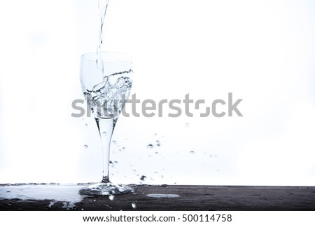 Filling glass with water fall on table