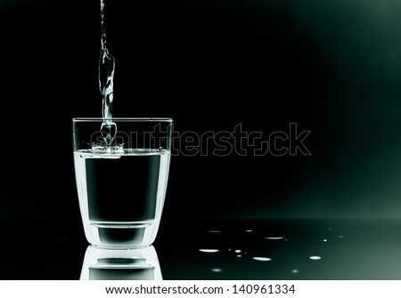 Filling in glass with water on black background - stock photo