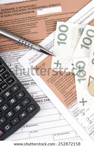 Filling in polish individual income tax form PIT with money and pen