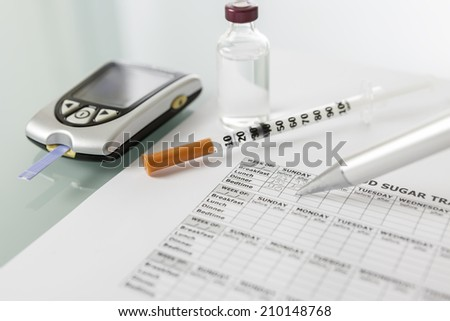 filling in the blood glucose diary with a pen and next a glucometer with a test strip a insulin vial and a syringe - focus on the center of the picture - stock photo