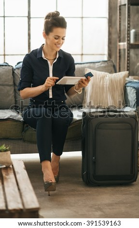 Filling inspired for adventure! Smiling elegant woman with credit card and ready for departure luggage ordering ticket online with tablet PC while sitting on sofa in loft apartment.