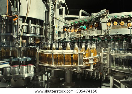 Filling of beer bottles on the conveyor in the plant.