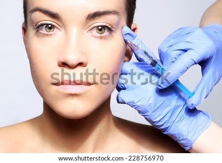 Filling of wrinkles, crow's feet, injection of botox.Portrait of a white woman during surgery filling facial wrinkles  - stock photo