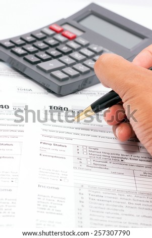 Filling out 2014 US Tax Form with ballpoint and calculator