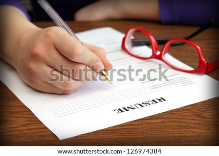 filling resume on wooden table, close-up - stock photo