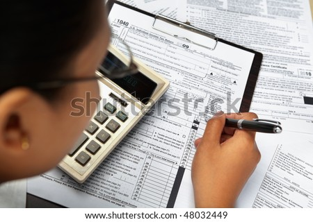 Filling 1040 tax form, surrounded with other document and a calculator