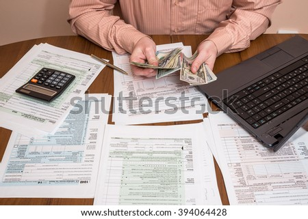 Filling 1040 tax form wtih laptop - stock photo