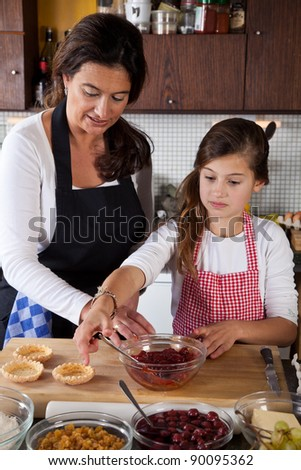 Filling the tarts with jam - stock photo