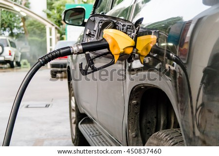 Filling up a black car with a yellow oil nozzle at the petrol station