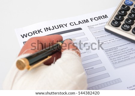 filling up a work injury claim form with a wrapped hand, medical and insurance concept - stock photo