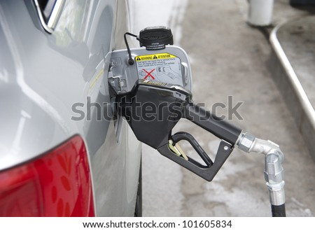 Filling up gas at fuel pump - stock photo