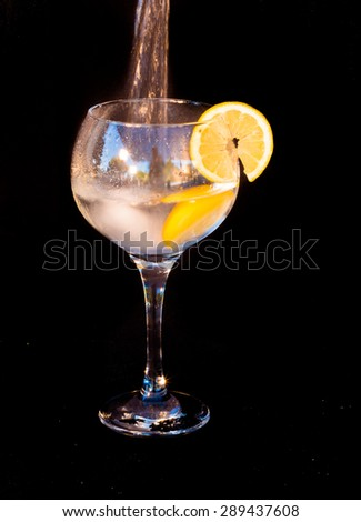 Filling up of gin and tonic drink isolated on black background - stock photo