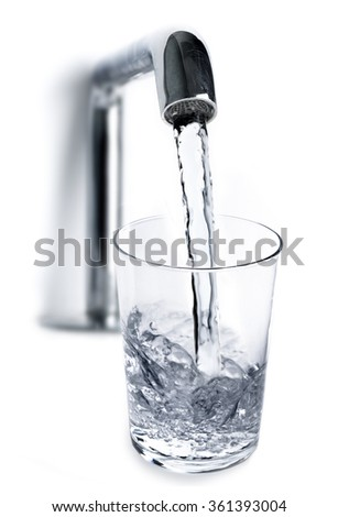 Filling water from the tap into a glass on white - stock photo