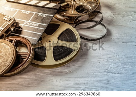Film camera chalkboard and roll on wooden table - stock photo