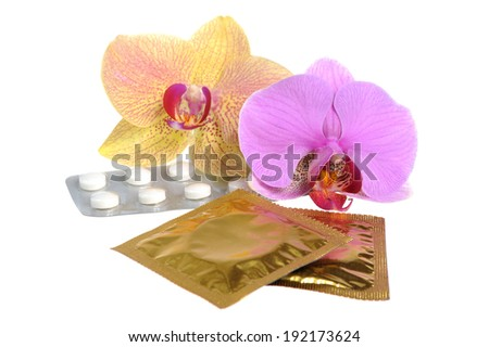Film-coated tablets and condoms with two orchid flowers isolated on white - stock photo