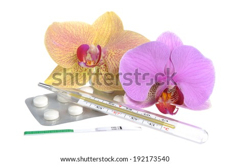 Film-coated tablets, mercury thermometer and ovulation test with two orchid flowers isolated - stock photo