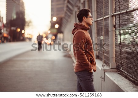 Film feel image of a man standing on a bridge looking forward over blurred bokeh urban city background
