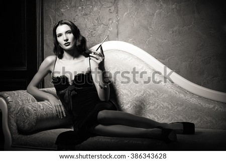 Film noir style: dangerous elegant young woman lying on a sofa and smoking cigarette. Black and white  - stock photo