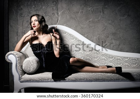 Film noir style: gorgeous beautiful young woman lying on a sofa and smoking cigarette  - stock photo