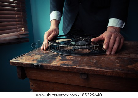 Film producer is handling a film reel in a projection room by the window - stock photo