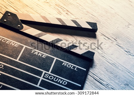 Film wooden camera chalkboard on wooden table - stock photo