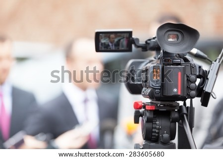 Filming an media event with a video camera - stock photo