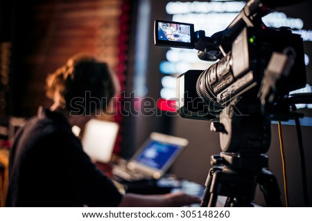 Filming creative video footage with professional video camera during the night - stock photo