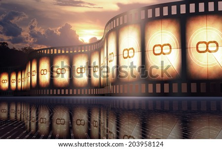 Filmstrip over the reflexive floor with sunset on the background. - stock photo