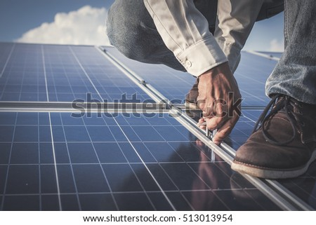 Filter and tone; engineer or electrician working on  maintenance equipment at industry solar power; engineer working on Wrench tightening solar mounting structure of photovoltaic panel