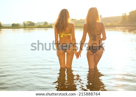 filtered image of 2 attractive young women or teenage girls best friends in bikini holding hands and looking at summer river or lake on outdoors copy space background - stock photo