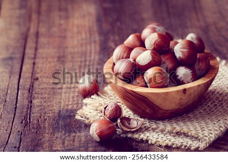 Filtered image of Hazelnuts in a wooden bowl on rustic background - stock photo