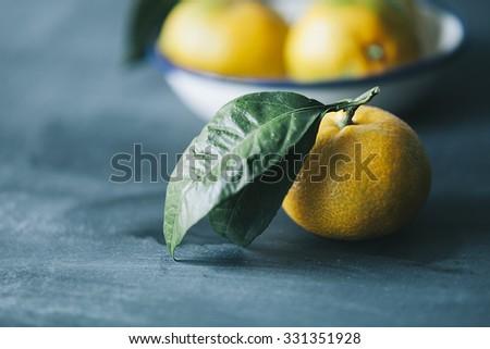 filtered photo of fresh mandarin fruits on dark blue wooden table - stock photo