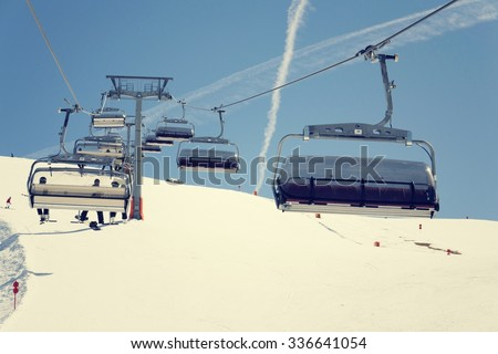 Filtered vintage photo of ski chair lift on sunny winter day