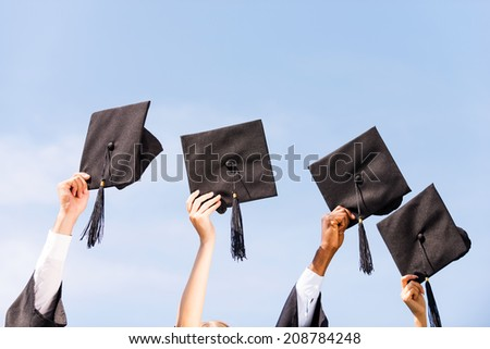 Finally graduated! Close-up of four hands holding mortar boards against sky background