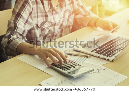 finance,accounting,Businessman analyzing investment charts with calculator laptop calculate technology in office,business, accounting,investment,analyzing data concept,selective focus,vintage color